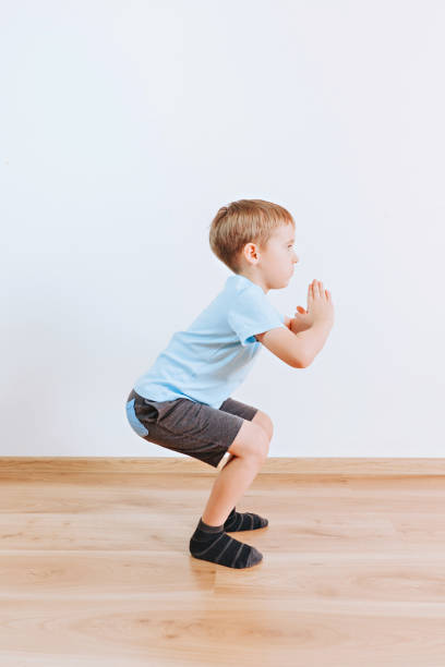 Kid boy performs exercises at home